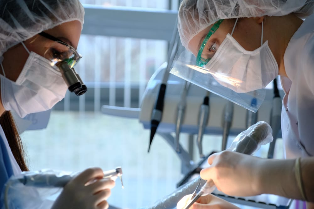 dental oral surgery on patient conducted by two dentists
