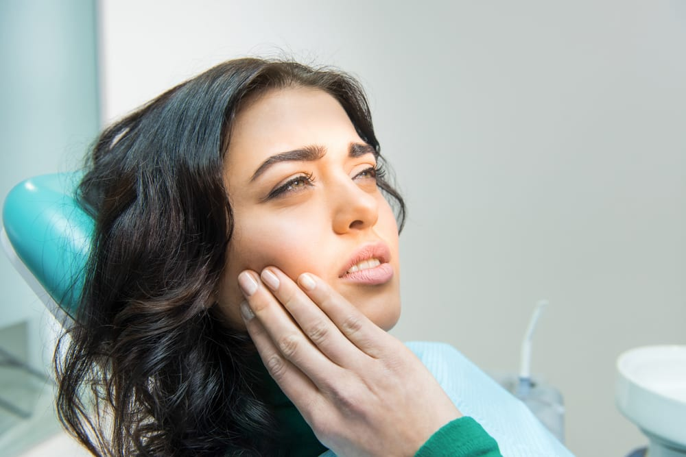 young woman sitting in dental chair with tooth pain