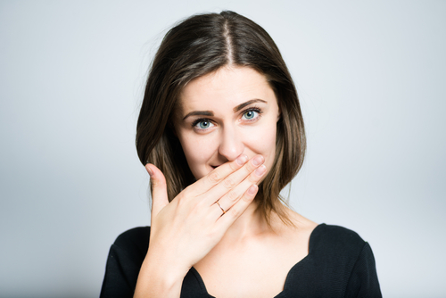 Woman covering her mouth in embarrassment