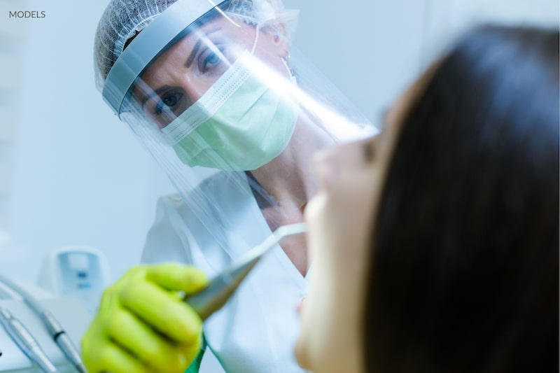 Dental hygienist cleaning a patients teeth while wearing PPE to protect from COVID