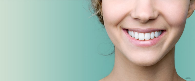Close-up of woman's smiling against a mint green background.